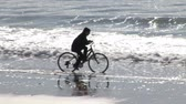 j��zda na kole : Stock Video Footage of a Woman Cycling on a Beach Dostupné videozáznamy