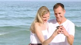 joy : Close-up of couple on the beach taking photos of themselves. Footage in high definition