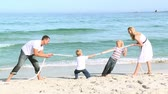 joy : Family having fun playing with a ball on the beach. Footage in high definition
