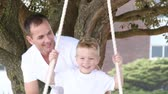 outside : Close-up of father and a son swinging in a park. Footage in high definition