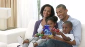 play : Footage in high definition of happy Afro-American family playing video games at home Stock Footage
