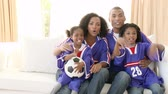 play : Footage in high definition of Excited Afro-American family watching a football match in the living-room
