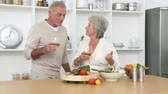 recipe : Footage in high definition of smiling senior couple preparing a salad in the kitchen and drinking wine Stock Footage