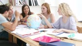 eğitim : Teenagers in a library working with a terrestrial globe and taking notes. Footage in high definition Stok Video