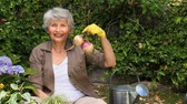 working parents : Old woman gardening and smiling at the camera in the garden Stock Footage