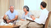 writing : Old couple talking with a comercial at home Stock Footage