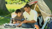 line : Father teaching the use of the fishing rod to his son sitting in front of a tent in the Park