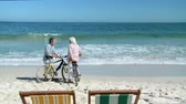stary : Elderly couple with bikes talking on the beach