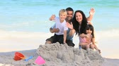 brother : Family waving hands to the camera on the beach Stock Footage