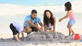 brother : Parents building a sand castle with their children on the beach
