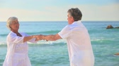 stary : Happy older couple dancing with joy on a beach Wideo