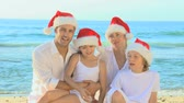 brother : Happy smiling family posing wearing Christmas hats on a beach
