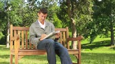 bulmaca : Young man doing crosswords while sitting on a park bench