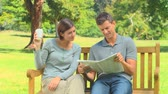 bulmaca : Young couple reading a newspaper while sitting on a bench in the park Stok Video