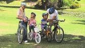 j��zda na kole : Young couple with their two children ready to go cycling in the park