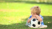 loiro : Young boy lying on the grass with his ball in the park Vídeos