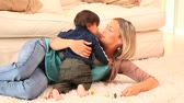 loiro : Woman playing with her baby lying on a carpet Vídeos