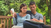 bulmaca : Young couple reading a newspaper together while sitting on a bench in the park