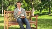 bulmaca : Young man doing a crossword on a bench in the park Stok Video