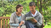 bulmaca : Young couple enjoying doing crosswords on a bench in a park