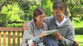 bulmaca : Young couple enjoying doing a crossword while sitting on a park bench