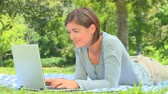 emberek : Young woman chatting on her laptop while lying on the grass in the park