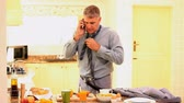 поздний завтрак : Man trying to get dressed while eating and receiving a call