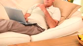 livingroom : Man lying on sofa working on laptop