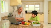 recipe : Woman giving her grandson a cookery lesson using a recipe from a laptop