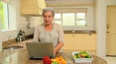 recipe : Retired woman looking up a recipe on her laptop in the kitchen