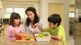 expression : Two children helping their mother in the kitchen with the cooking Stock Footage