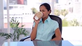 tied up : Well-dressed woman drinking a coffee in a bright office