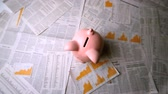 ceramic : Pink piggy bank falling over sheets of paper with numbers and graphs in slow motion