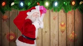against : Digital animation of Santa carrying sack of gifts against festive wooden background