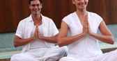 zen like : Smiling couple in white sitting in lotus pose with hands together at the health spa Stock Footage