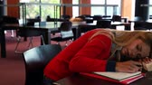 campus : Mature student sleeping at study table in library Stock Footage