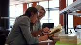 campus : Two mature students studying together in library