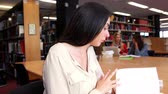 campus : Students working around a table with one looking at camera in library Stock Footage