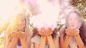 paint : Young women having fun with powder paint on a sunny day in slow motion