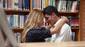 book : Student couple hugging in the libraryat the college Stock Footage
