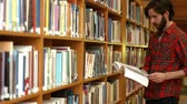 silence : Student reading a library book by the book shelf Stock Footage