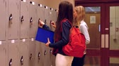 skříňku : Two happy students chatting to each other while opening lockers