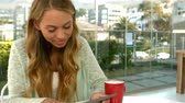 strong tea : Pretty girl using tablet and smiling at the camera in slow motion Stock Footage