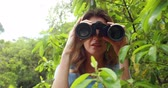 finding : Smiling woman with binoculars behind leaves in the countryside Stock Footage