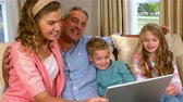 caucasian : Smiling family using technology on sofa in slow motion