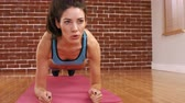 caucasian : A fit woman on a plank position in fitness studio