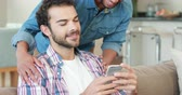 caucasian : Gay couple on smartphone together in living room Stock Footage