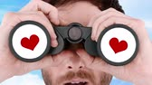 caucasian : Man looking through binoculars with heart Stock Footage