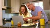 caucasian : Happy couple using laptop in kitchen in slow motion