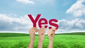 affirmative : Hands holding up yes against blue sky and green field Stock Footage